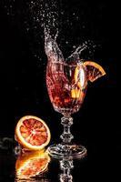 pezzi di arancia rossa che cadono in un bicchiere con acqua specchiata su sfondo nero foto