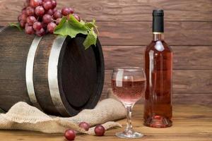 botte di legno con bottiglia di vino e vetro foto