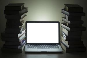 portatile con libri impilati scuri foto