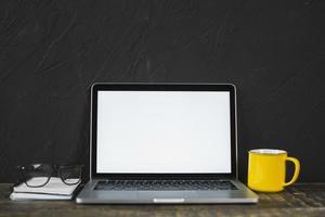 portatile e occhiali con tazza da caffè gialla e diario sul tavolo foto