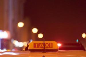 segno di taxi sul tetto dell'auto su uno sfondo sfocato foto