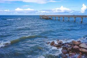 paesaggio marino che si affaccia sul lungo molo della località turistica con persone che camminano. foto