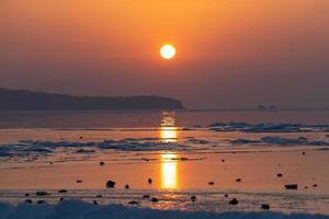 vista sul mare spiaggia di ghiaccio e il tramonto rosso. foto