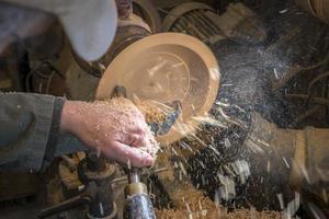 fare una ciotola di legno su un tornio in un vecchio piccolo laboratorio foto