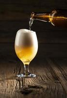 versando la birra in una tazza foto