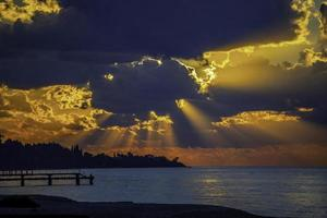 paesaggio marino con un tramonto luminoso e raggi tra le nuvole foto
