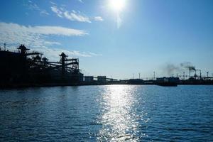 silhouette di strutture industriali sullo sfondo del mare foto