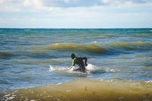un surfista solitario si allena su piccole onde nel mar baltico foto