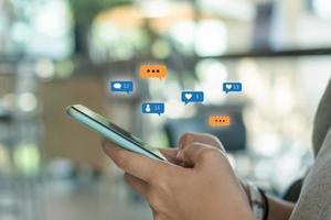 donna che tiene uno smartphone per utilizzare i social media con le icone di comunicazione. concetto di tecnologia. foto