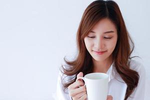 Ritratto di giovane donna asiatica in possesso di una tazza di caffè su uno sfondo bianco. foto