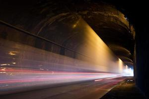 un tunnel buio con scie luminose foto