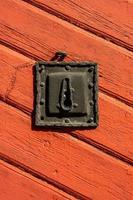 vecchia serratura della porta di ferro su una porta di legno rossa foto