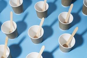 bicchieri di carta e cucchiai di legno distesi foto