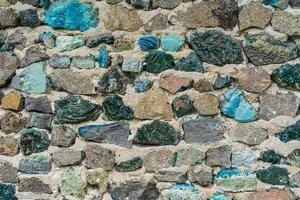 vecchio muro di roccia con pietre colorate foto