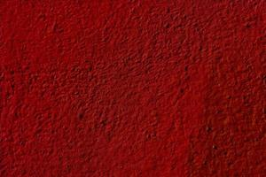 fondo rosso strutturato dell'intonaco della parete foto