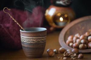 tazza e le nocciole noci sparse su una superficie di legno. foto