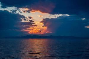 vista sul mare con un tramonto drammatico scuro foto