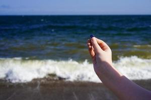 mano del bambino con vetro di mare sullo sfondo del mare. foto