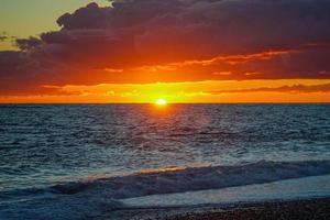 drammatico tramonto infuocato sul paesaggio del mare. foto