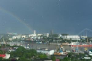 sfondo astratto con il paesaggio urbano attraverso il vetro con gocce di pioggia foto