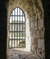 finestra di un'antica fortezza contro un muro di mattoni foto