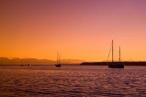 barche a vela al tramonto sulla costa occidentale della British Columbia foto