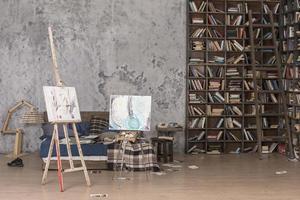 due tele per dipingere vicino a libri sugli scaffali foto