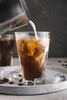 latte che versa nel bicchiere con il caffè foto