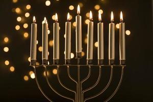 menorah con candele vicino a luci ghirlande astratte foto