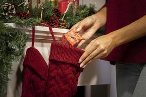 persona che mette il regalo nella calza di Natale foto