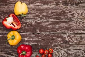 peperoni gialli rossi e pomodorini sullo scrittorio di legno foto