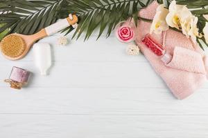 asciugamano con sale e pennello con fiori e foglie su fondo in legno foto