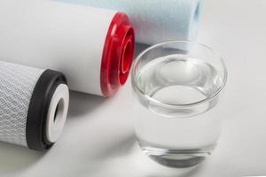 filtri per l'acqua e bicchiere d'acqua su sfondo bianco foto