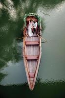 una gita in barca per un ragazzo e una ragazza lungo i canali e le baie del fiume foto