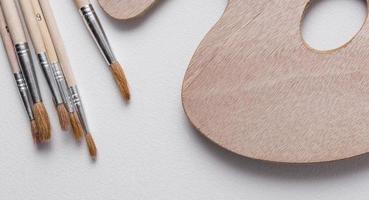 spazzole e cavalletto in legno su sfondo bianco foto