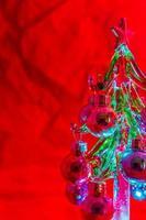 mini albero di natale in vetro illuminato e impostato su uno sfondo rosso foto