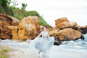sposa in un vestito di luce blu che cammina lungo l'oceano foto
