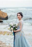 sposa con un mazzo di fiori sulla spiaggia foto