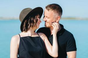 giovane coppia un ragazzo con una ragazza in abiti neri stanno camminando sulla sabbia bianca foto