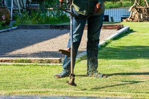 Chiudere le gambe del giardiniere falciare l'erba in un giardino esterno con strumenti di falciatura in una giornata di sole foto