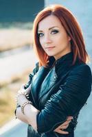 ragazza dai capelli rossi in una giacca nera e occhiali blu foto