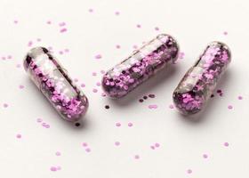 pillole glitter su sfondo bianco foto