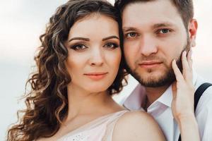 giovane coppia un ragazzo in calzoni neri e una ragazza in un vestito rosa stanno camminando lungo la sabbia bianca foto