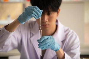 asiatico giovane scienziato test di laboratorio e analisi chimiche presso il laboratorio foto