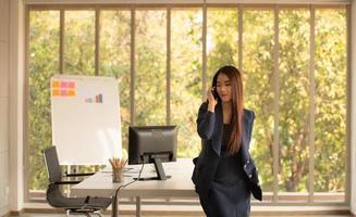 donna asiatica di affari che per mezzo del telefono cellulare in un ufficio foto