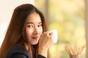 donna asiatica di affari che beve caffè in un ufficio foto
