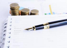 pila di monete e penna stilografica di affari sul rapporto del documento foto