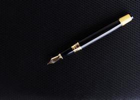 Close up della penna stilografica sulla copertina in pelle del libro di sfondo foto