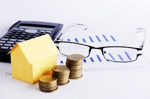 concetto di mutui per la casa con pila di monete e calcolatrice di carta casa e occhiali foto