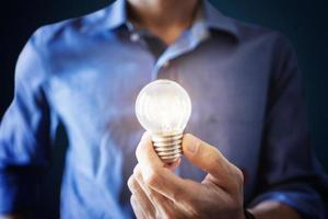 nuove idee, innovazione e concetto di ispirazione. un uomo in camicia blu che tiene la lampadina incandescente foto
